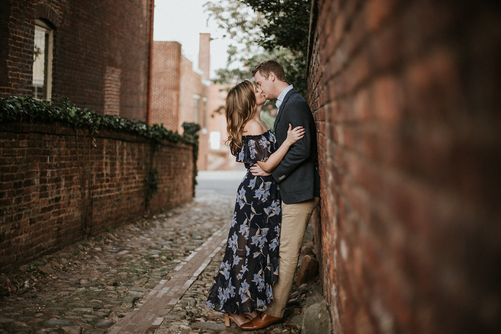 Couple kissing in alleyway against wall