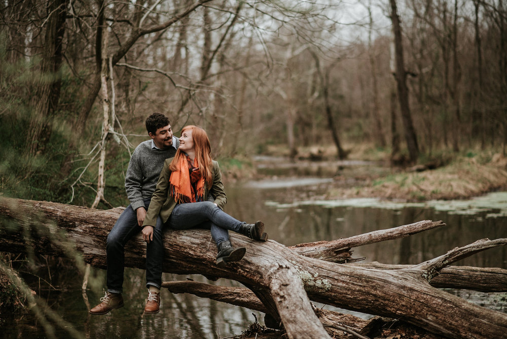 Couple sitting on fallen tree over water