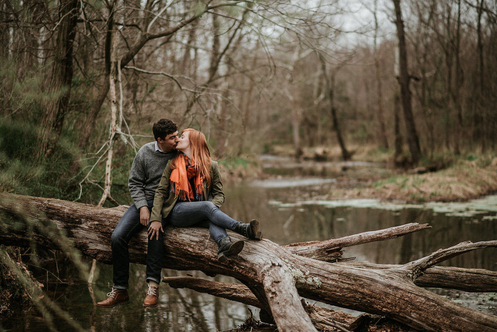 Couple kissing on fallen tree in water