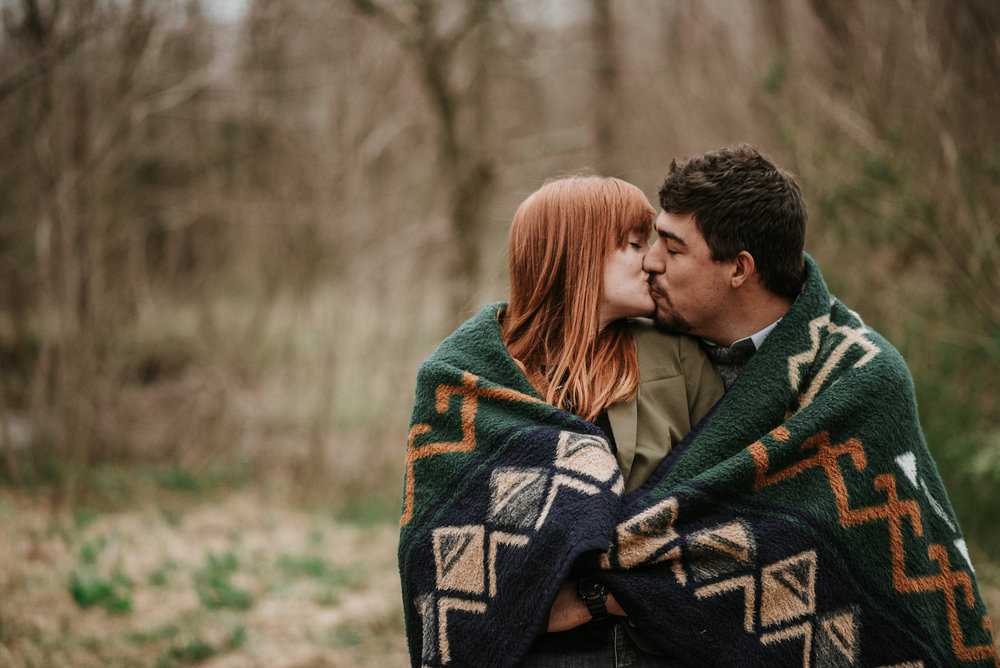 Couple wrapped up in blanket, kissing