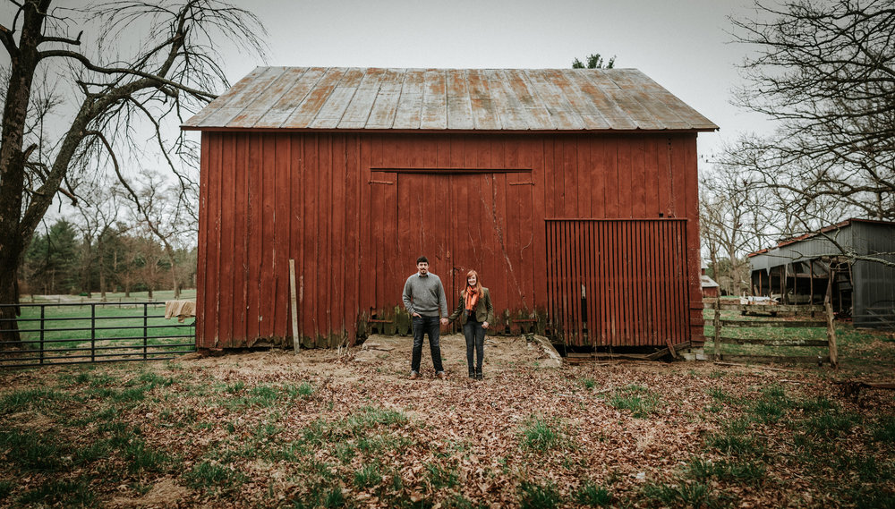 Couple standing in front of red barn