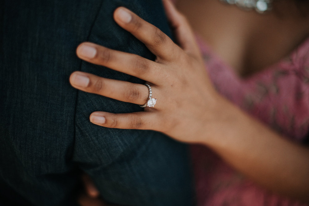 Woman's hand with engagement ring on man's arm