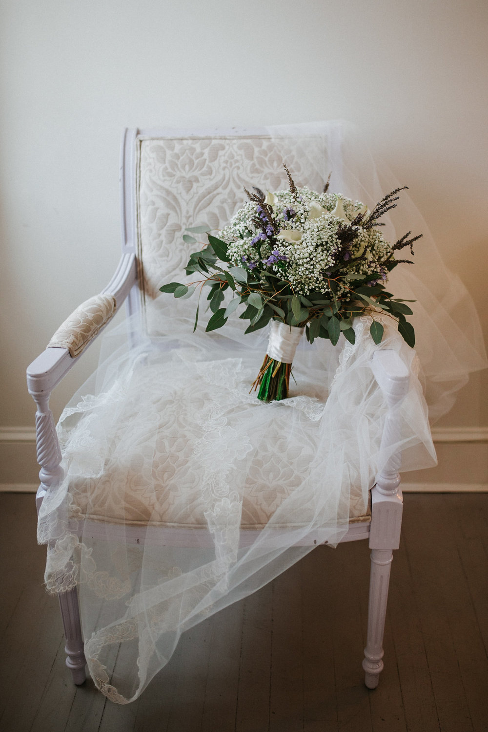 Bride's wedding bouquet on chair with veil