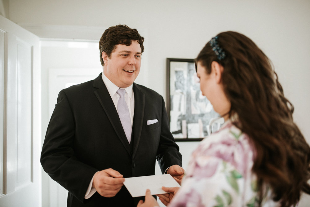 Groomsman delivering letter to bride