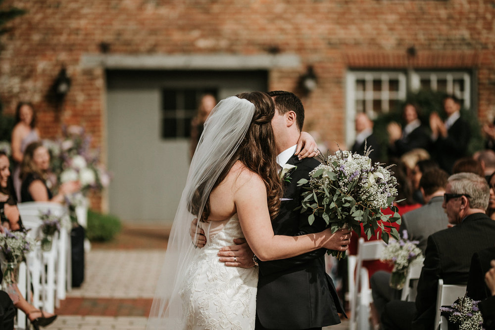 Bride and groom kissing at end of aisle