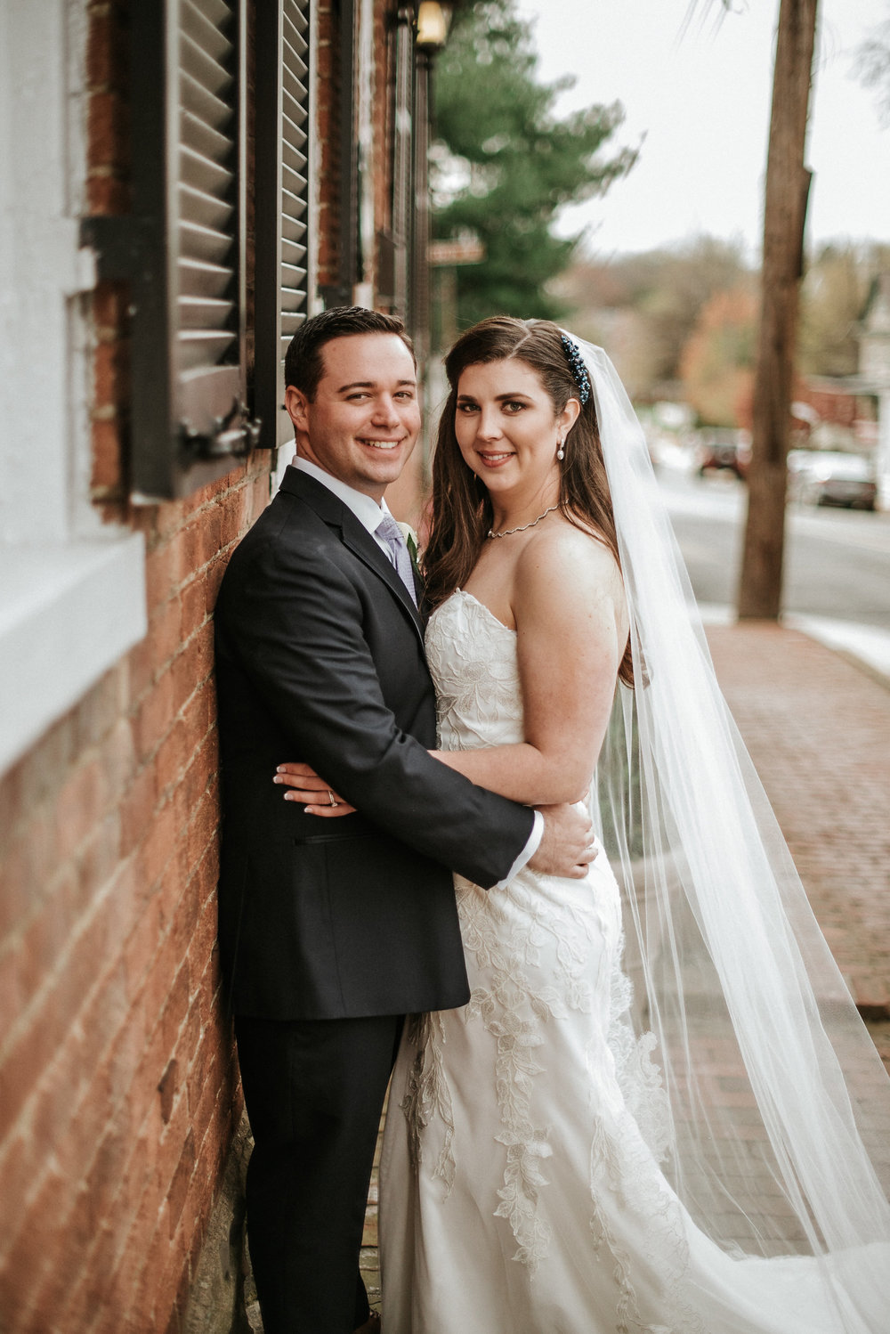 Groom and bride leaning against brick wall