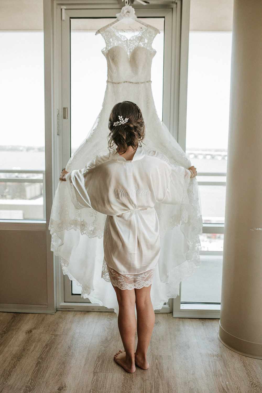 Bride in robe looking at wedding dress