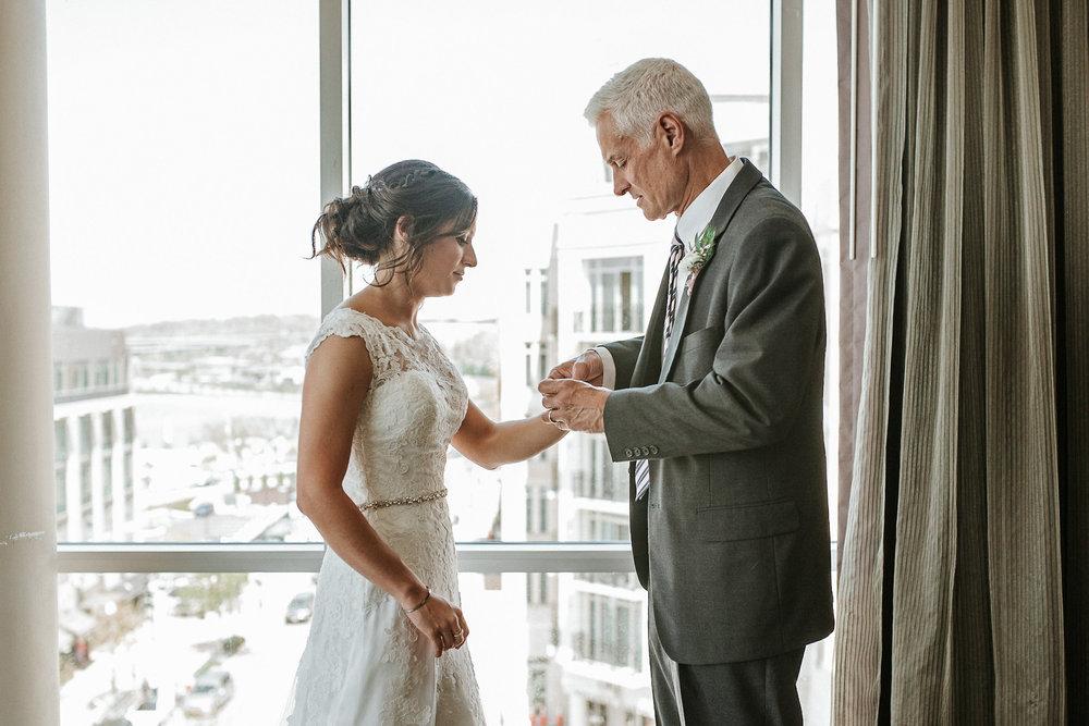 Father fastening bride's bracelet