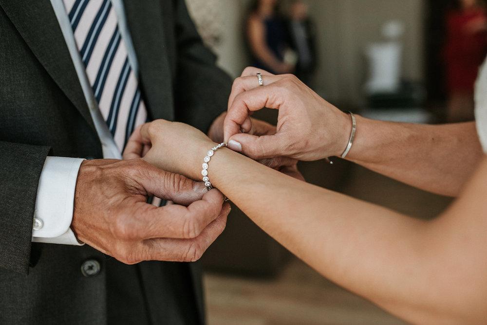 Father giving bride a bracelet
