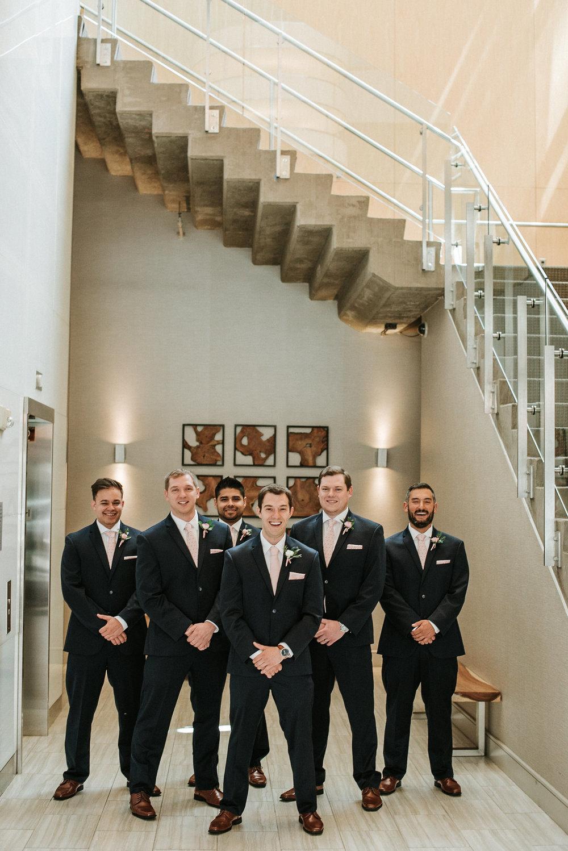Groom and groomsmen under stairs