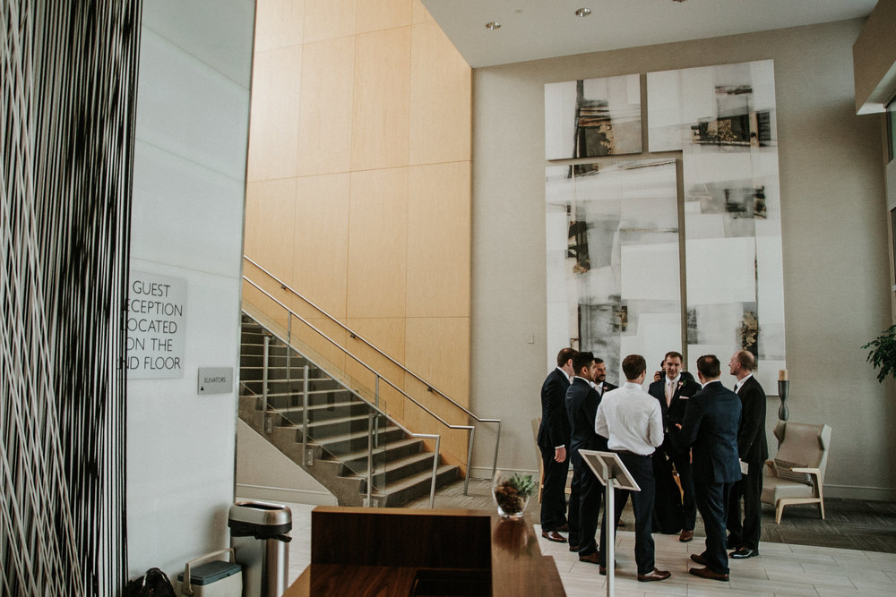Groomsmen standing in hotel lobby