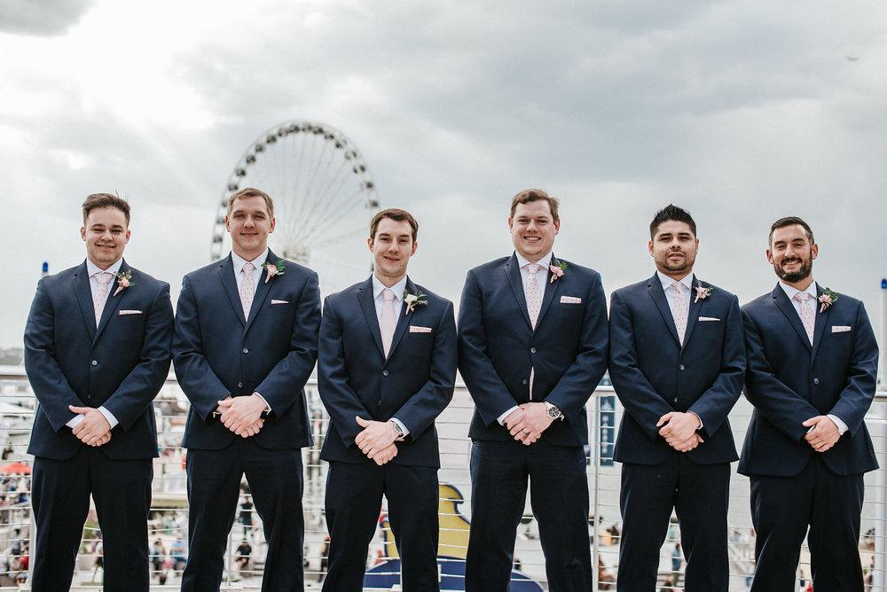 Groomsmen in front of ferris wheel