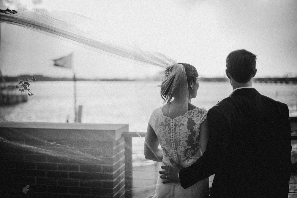 Bride and groom overlooking water