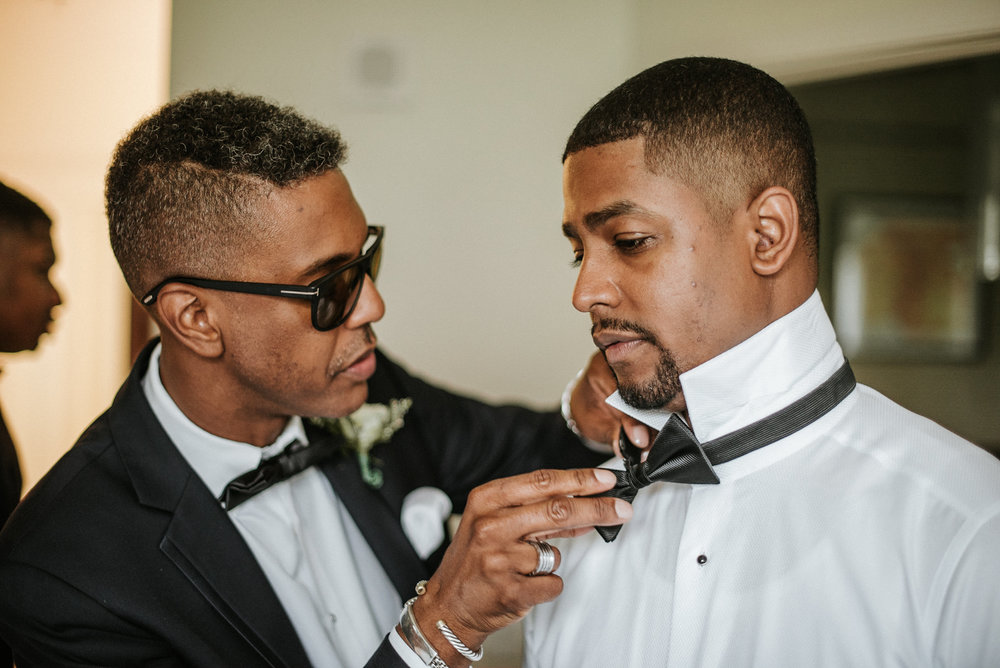 Groomsmen helping groom with bow tie