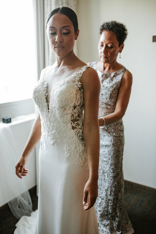 Mother buttoning wedding dress