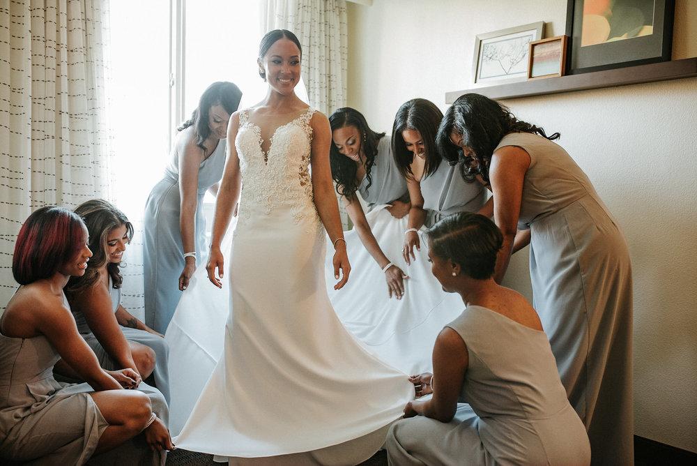 Bridesmaids straightening bride's dress
