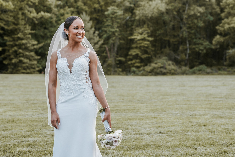 Bride standing in field with bouquet