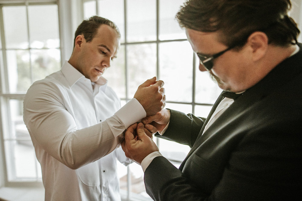 Groomsmen helping groom with cufflinks