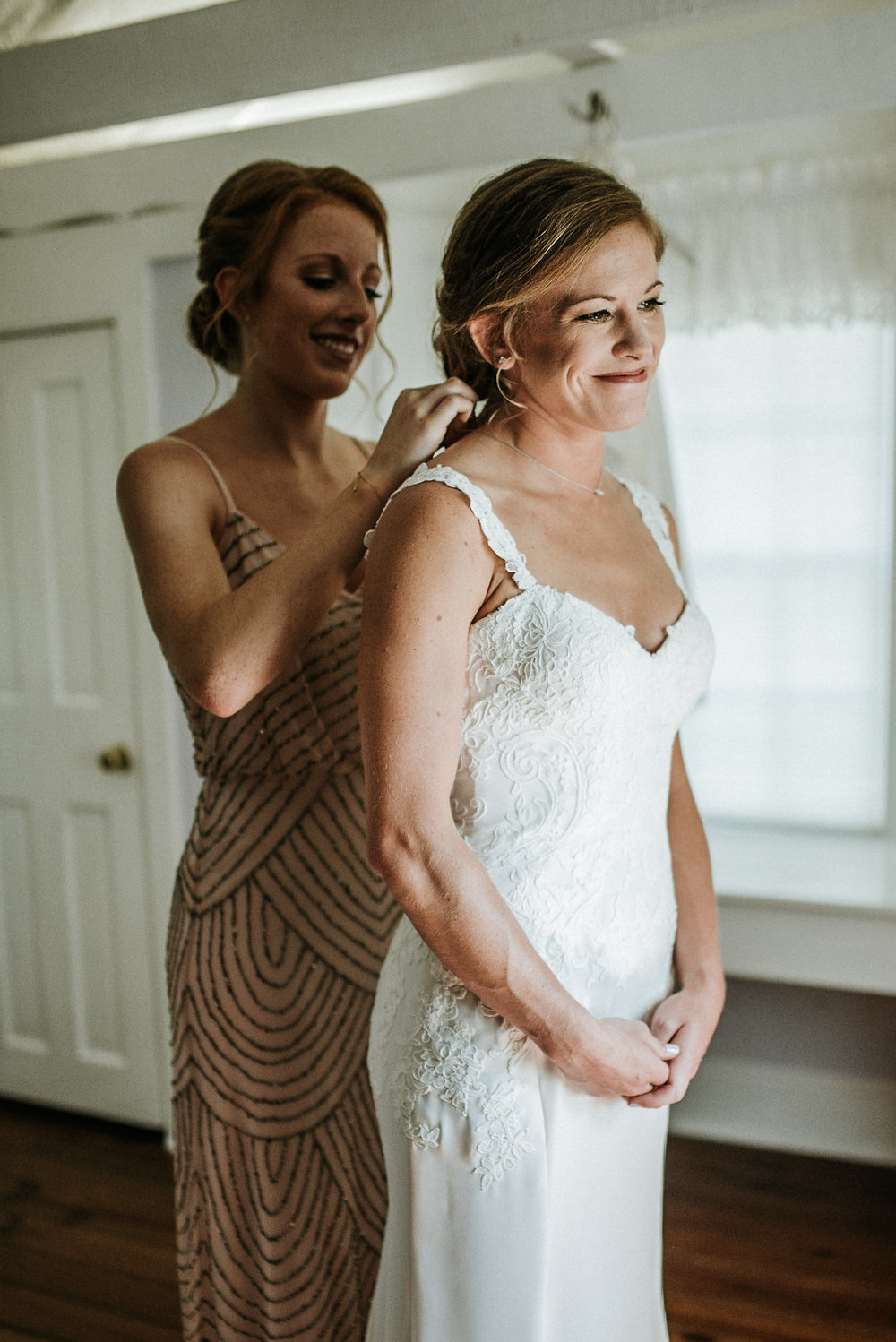 Bridesmaid putting on bride's necklace