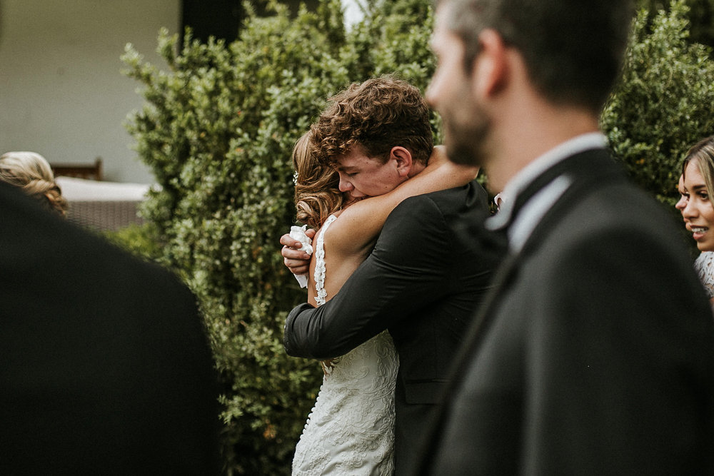 Bride hugging groomsman