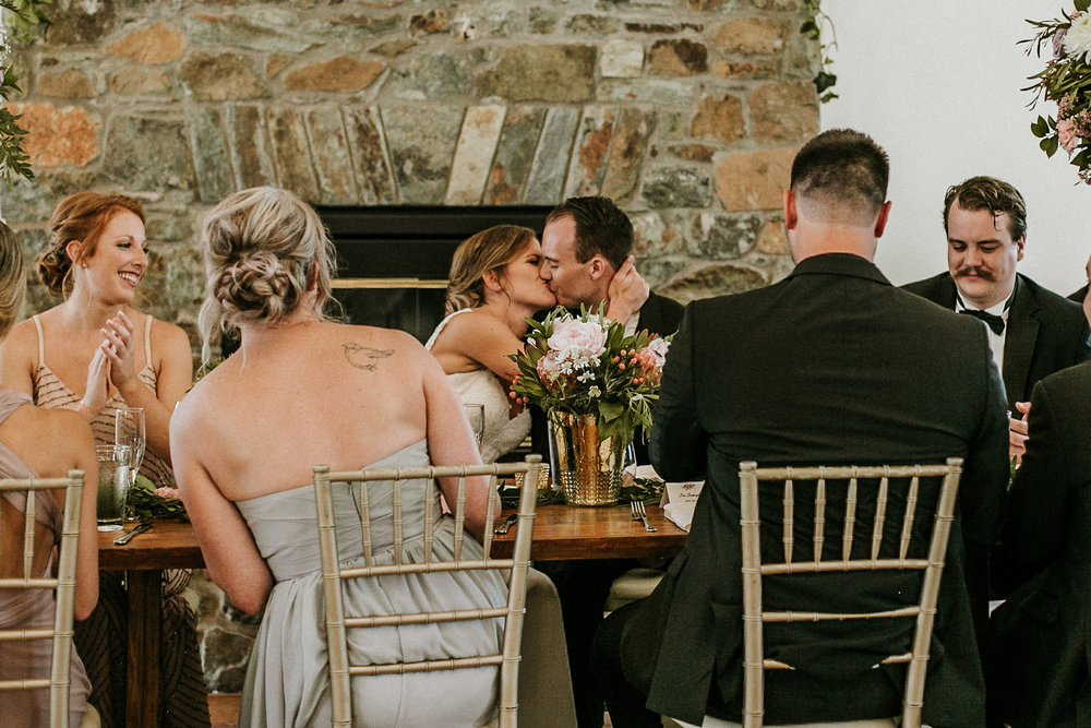 Bride and groom kissing during reception dinner