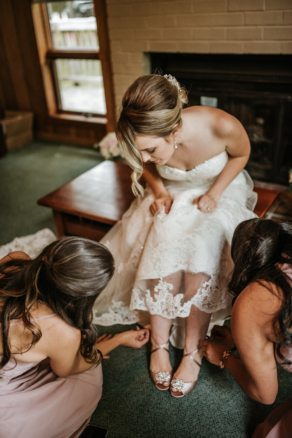 Bridesmaids helping bride with shoes
