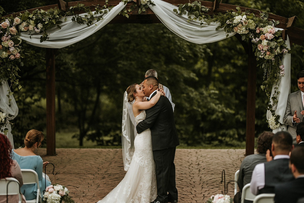Bride and groom kissing at wedding