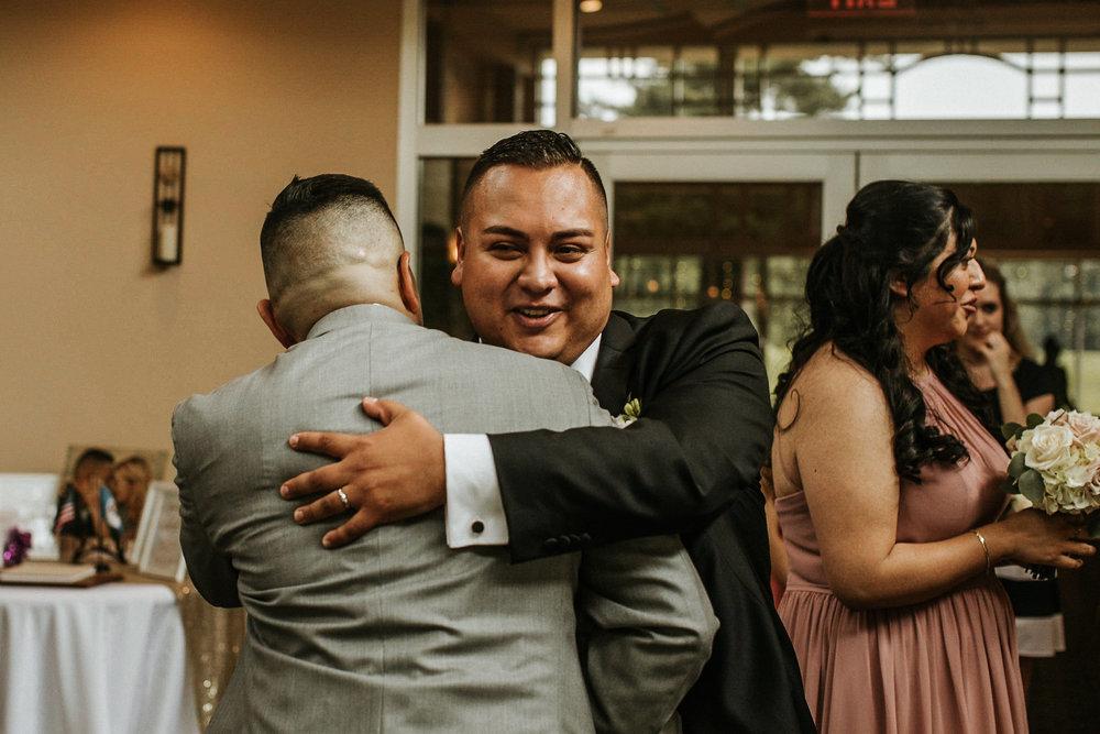 Groom hugging groomsman