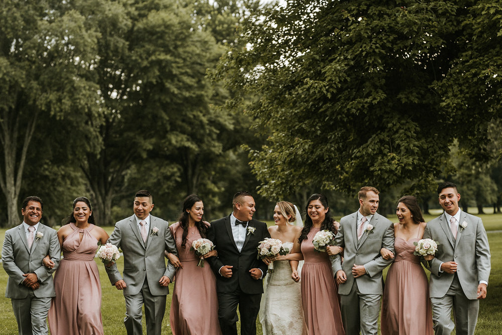 Bridal party linking arms for photo