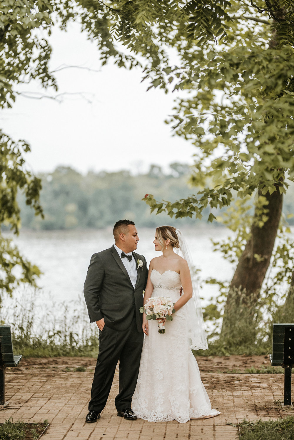 Bride and groom looking at one another in front of lake