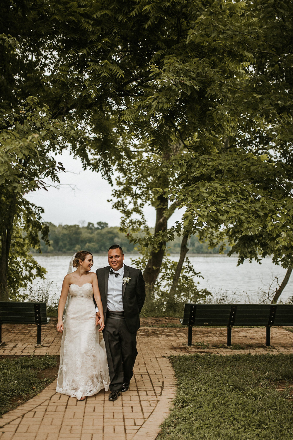Bride and groom walking away from lake