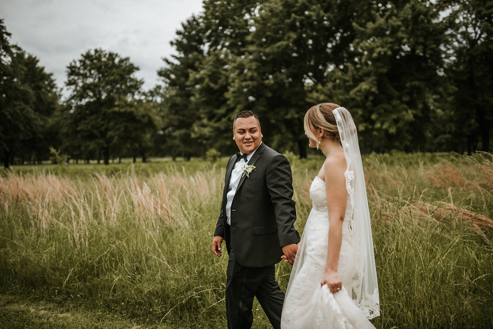Bride and groom walking in front of field