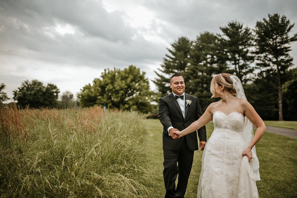 Bride leading groom through field