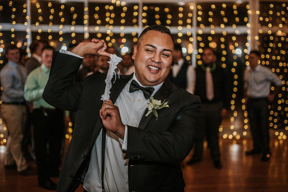Groom garter toss at reception