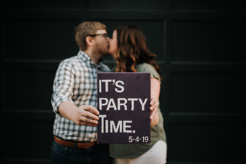 Engagement photo with party signage