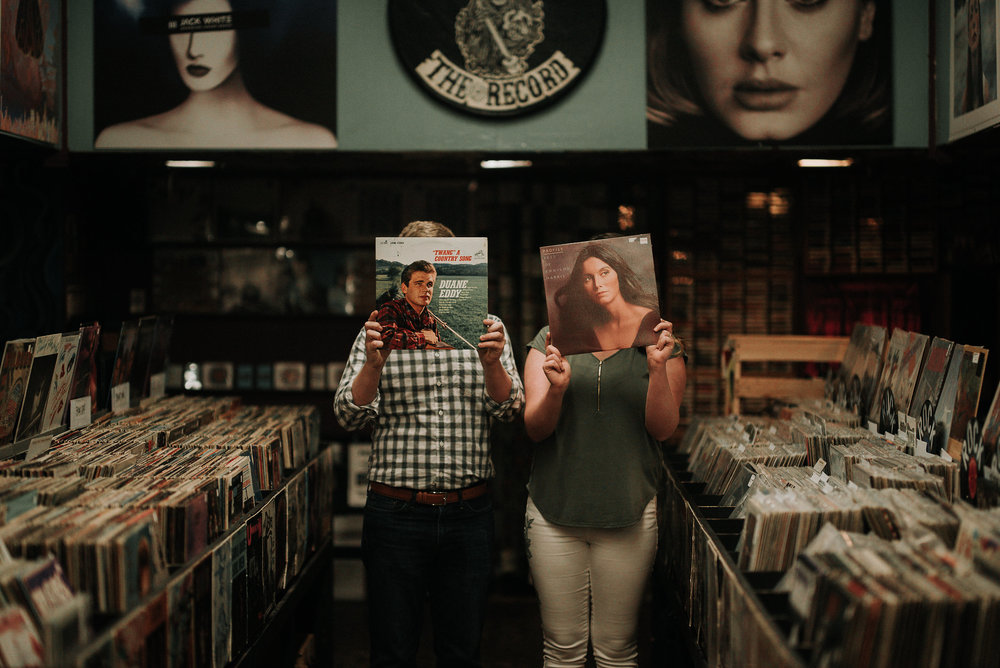 Couple holding records in front of faces