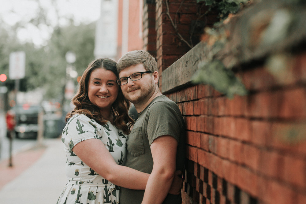 Couple hugging against brick wall