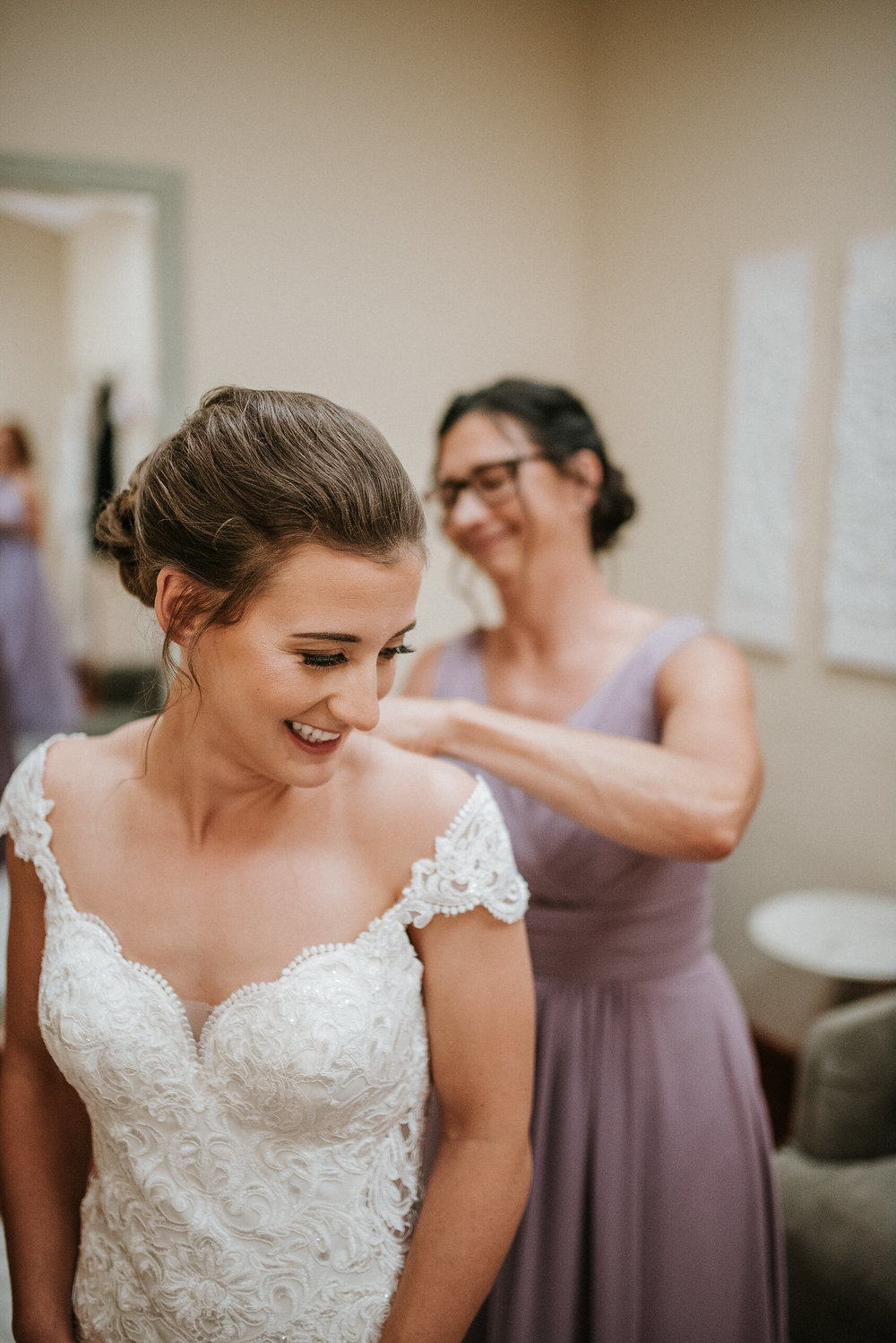 Mom buttoning bride's dress