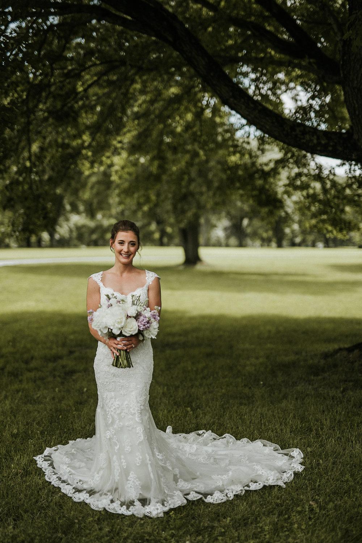 Bride posing under tree
