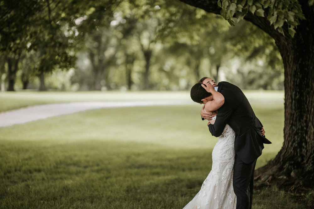 Bride and groom hugging under a tree