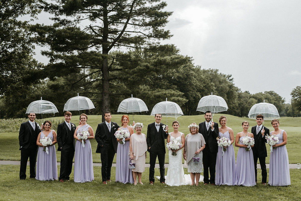 Bridal party under clear umbrellas