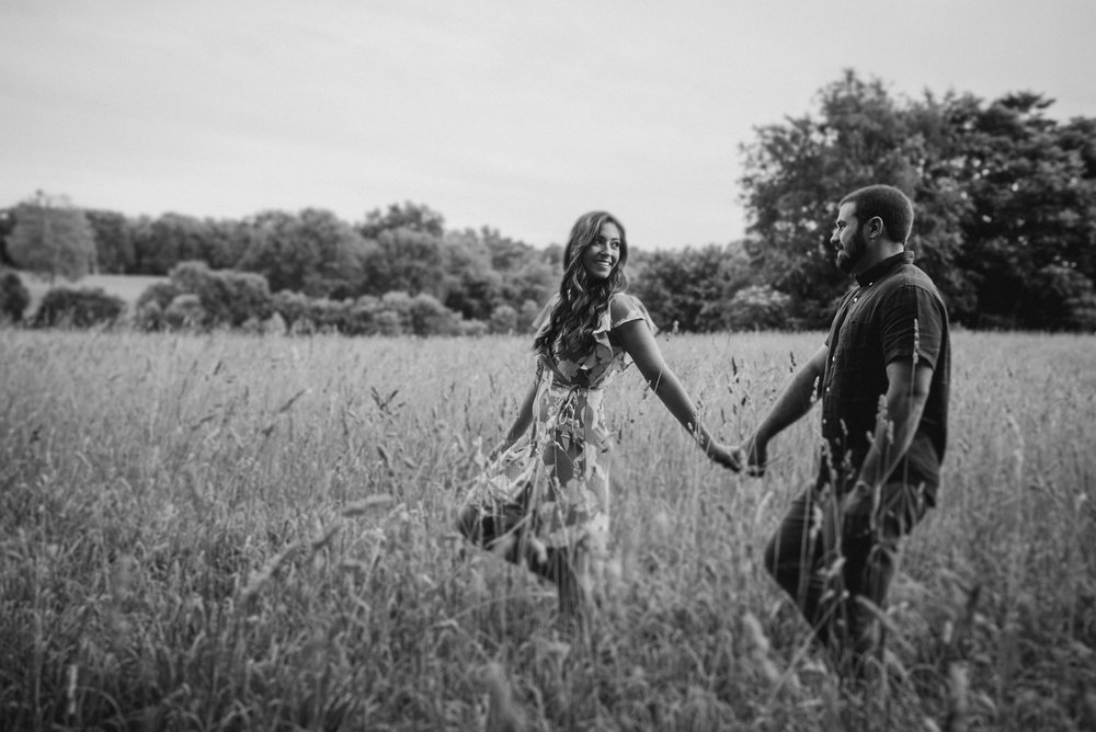 Couple walking through field in black and white
