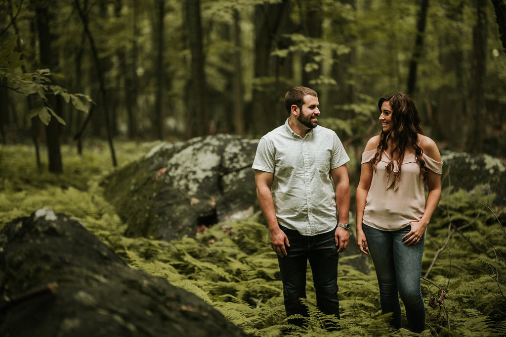 Couple standing in mossy forest