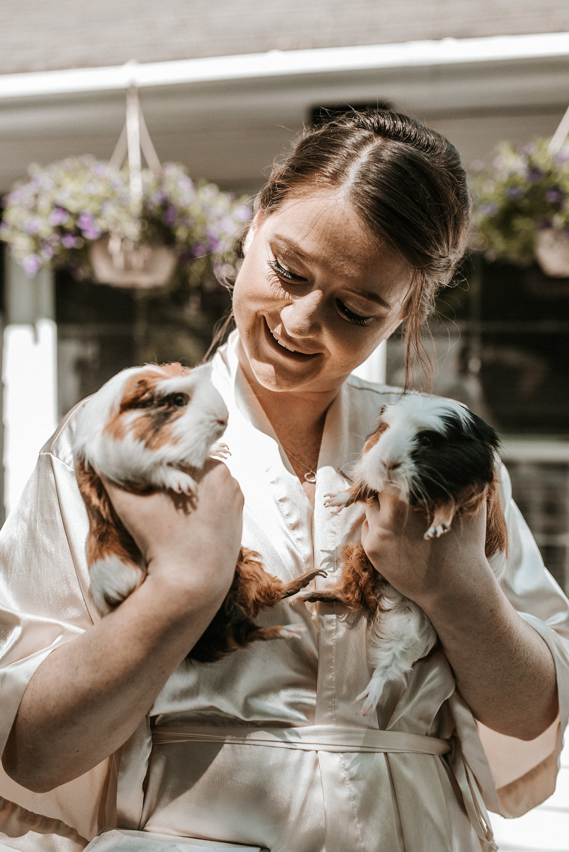 Bride holding guinea pigs