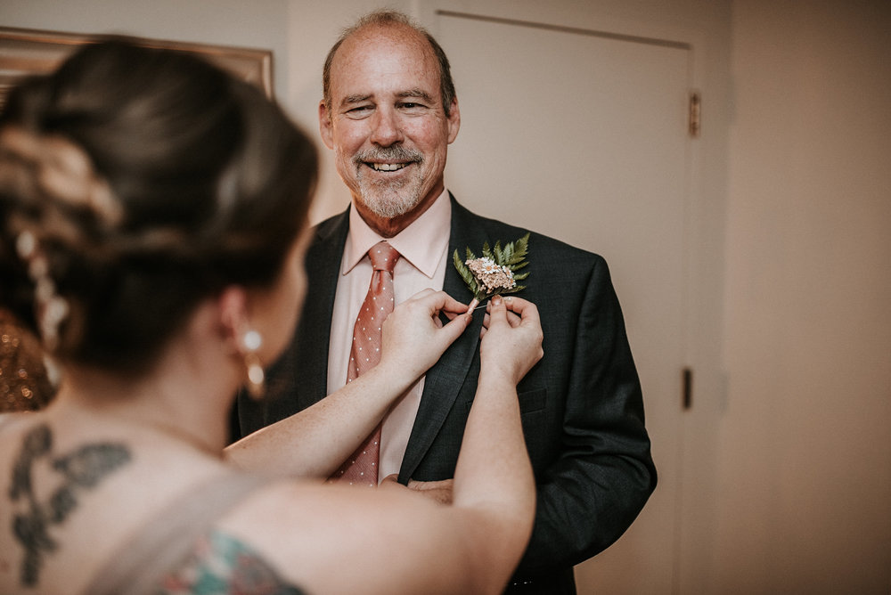 Bride pinning flower on father