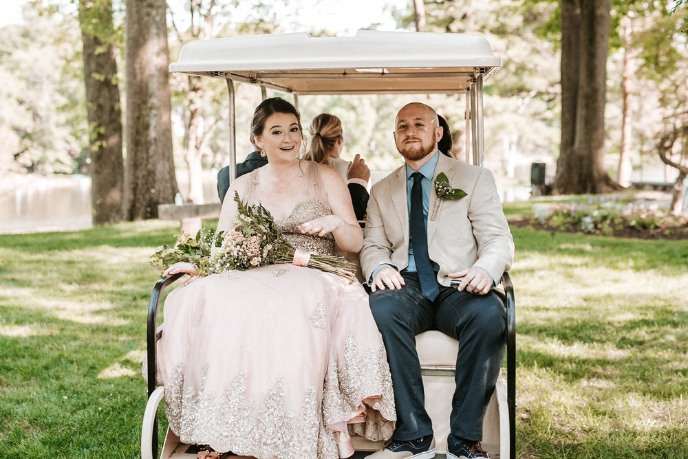 Bride and groom riding in golf cart