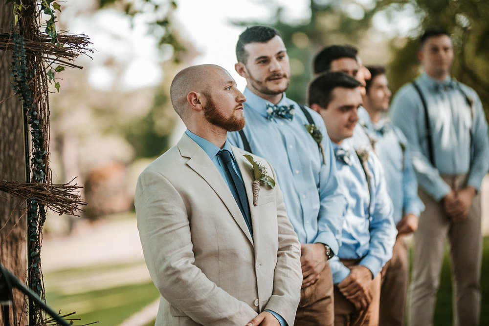 Groom standing at front of aisle