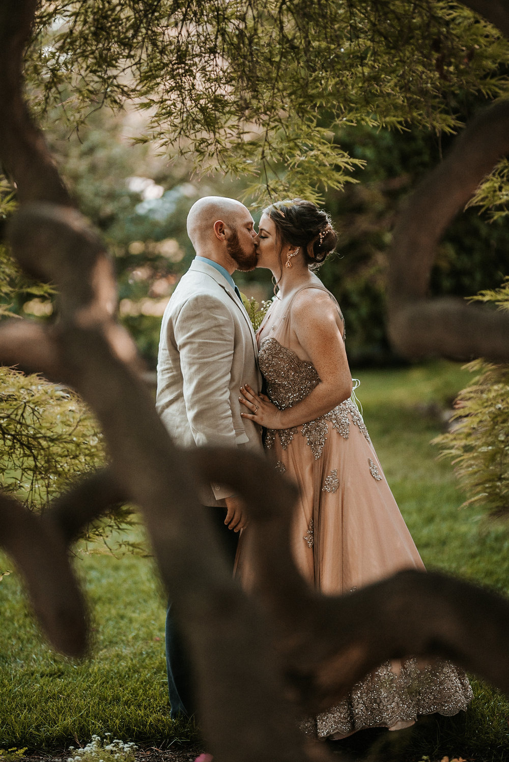 Bride and groom kissing behind tree