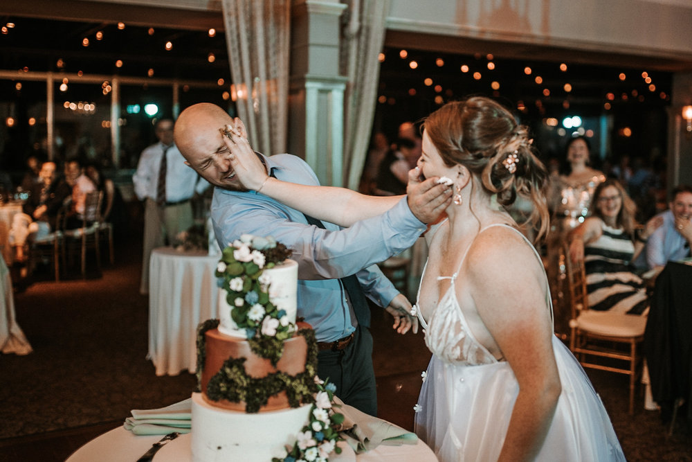 Bride and groom smashing cake