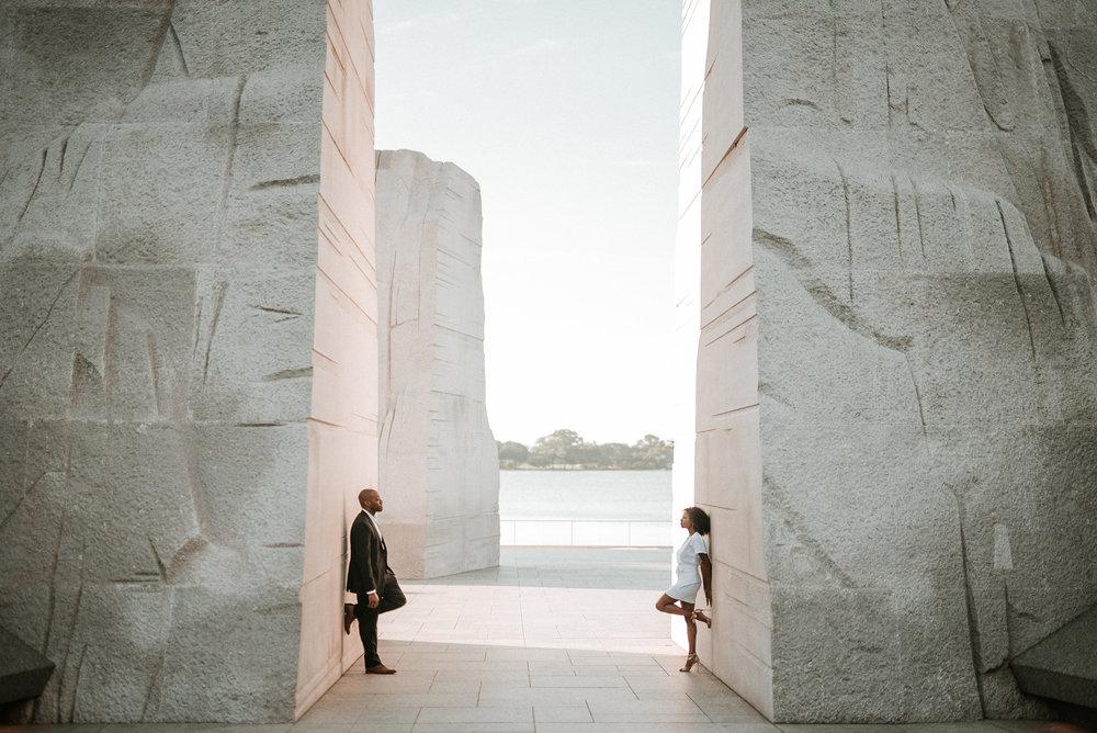 Couple posing against stone memorial